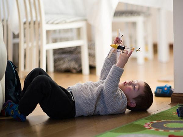 Trẻ  chơi máy bay khi ở nhà một mình
